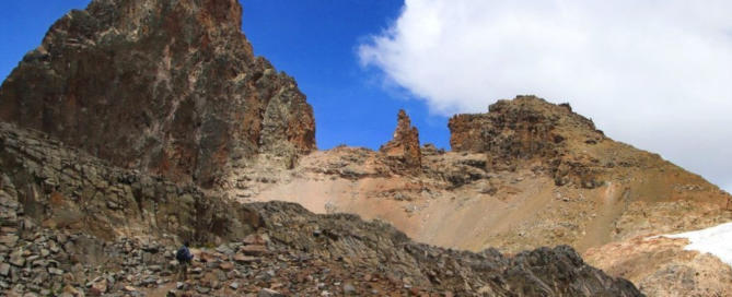 Reddish-brown rocky peak with patch of snow on Mount Kenya