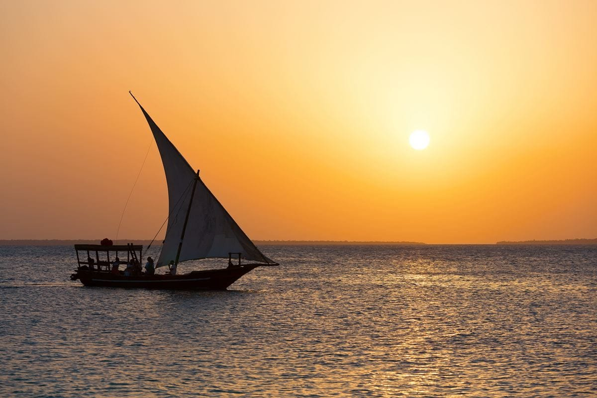 a dhow sailboat off coast of Zanzibar with sunset in background